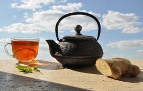 Фото: Чайник, чашка чая и корень имбиря.