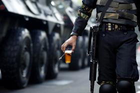 Фото: Солдат несет чай мимо броневика президента. Джакарта, Индонезия.